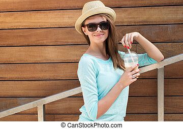 Pretty Woman with Smoothie Leaning Against Rail