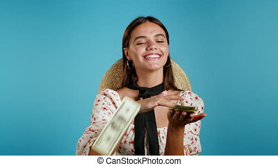 Pretty woman with surprised happy face scatters, waste money. Girl overspend US currency. Lady is flush with dollars on blue studio background . High quality 4k footage