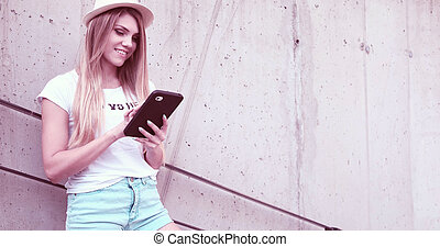 Pretty Woman with Tablet Leaning Against the Wall