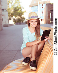 Pretty Woman with Tablet Sitting on a Modern Chair