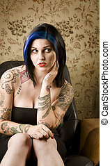 Pretty Woman with Tattoos in a Leather Chair