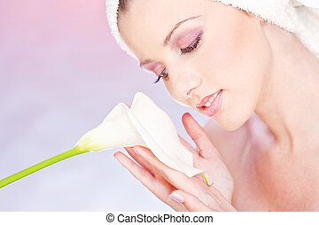 pretty woman with towel gently holding a white flower