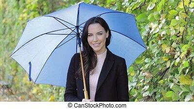 Pretty woman with umbrella - Pretty smiling woman in black...