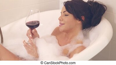 Pretty woman with wine in bath - Horizontal indoors shot of...