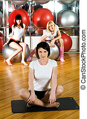 Pretty woman with yoga mat in fitness center