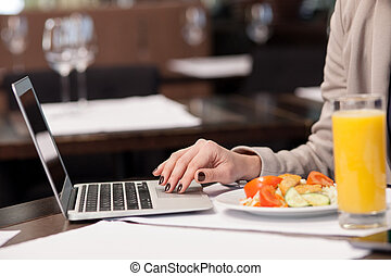 Pretty woman working with a notebook in restaurant - Close...