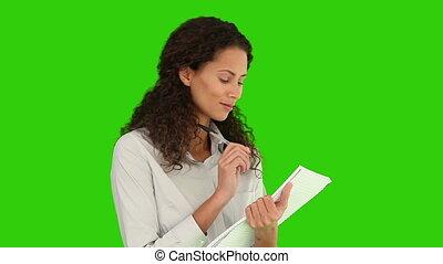 Pretty woman writing down somethings against a green screen