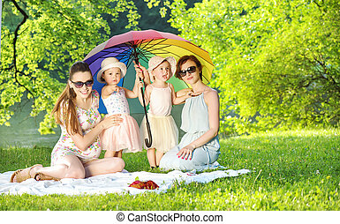 Pretty women and little girls resting on the blanket