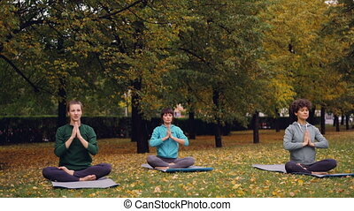 Pretty women are relaxing sitting in lotus position on yoga...