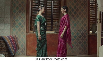 Pretty women in sari meeting and greeting each other -...