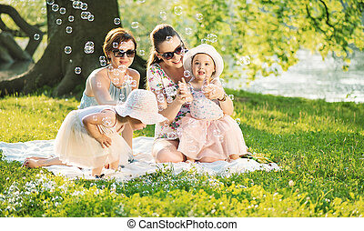 Pretty women resting on the blanket with little daughters