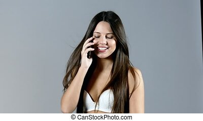 Pretty young adult woman speaks on phone and smiles