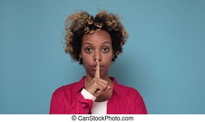 Pretty young African American woman makes silence gesture, presses index finger to lips. Slilence please. Strict female makes hush sign