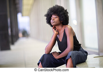Pretty young African American woman on city streets, sitting on the bench
