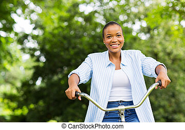 young african american woman riding a bike in forest
