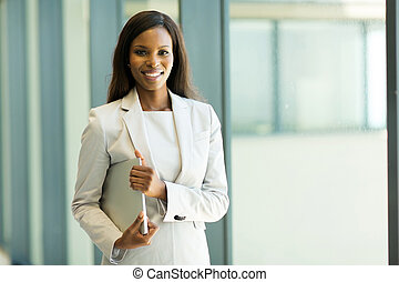 young african office worker holding laptop