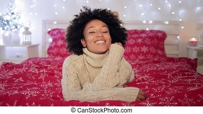 Pretty young African woman in a festive bedroom