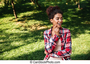 Pretty young african woman sitting outdoors in park