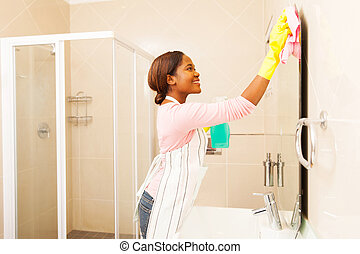 young african woman wiping bathroom mirror