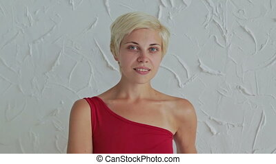 Pretty, young and blonde woman in red dress without make-up looking at camera