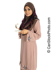 Pretty young Asian Muslim woman with a cup of coffee or tea in action. Islamic fashionable attire concept