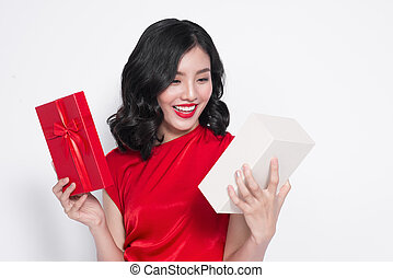 Pretty young asian woman dressed in red dress with a present