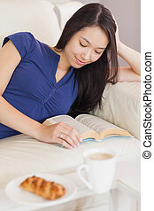 Pretty young asian woman lying on the sofa reading a book