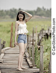Pretty young asian woman walking on wood bridge