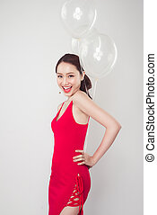 Pretty young asian woman wearing red dress with balloons in hand.