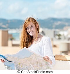 Pretty young au-pair studying a map