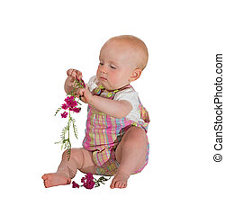 Pretty young baby playing with flowers
