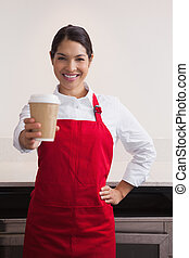 Pretty young barista offering cup of coffee to go in a cafe
