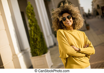 Pretty young black woman with curly hair on the street