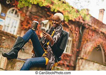 Pretty young black woman with mobile phone