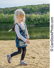 Pretty young blond girl running on a sandy beach