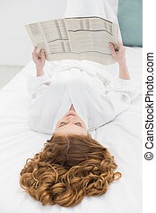 Pretty young blond reading newspaper in bed