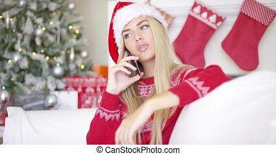 Pretty young blond woman chatting on her mobile phone