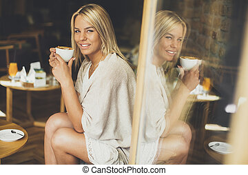 Pretty young blond woman sitting in the cafe