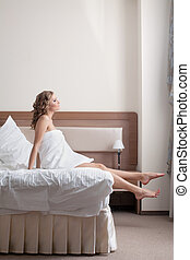 pretty young blond woman stand from bed