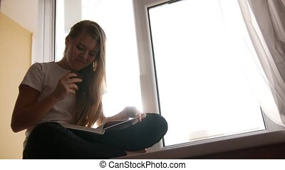 Pretty young blonde girl eats cake and flipping through the...