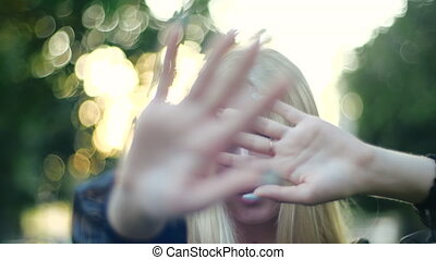 Pretty young blonde with long hair and manicure covers her face with both hands, leading in different directions on blurred background of trees and shining sun in park, close-up view in slow motion.