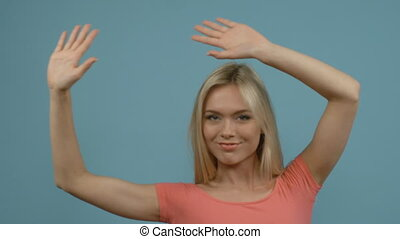 Pretty young blonde woman in fitting pink dress dancing with hands up, blue studio background