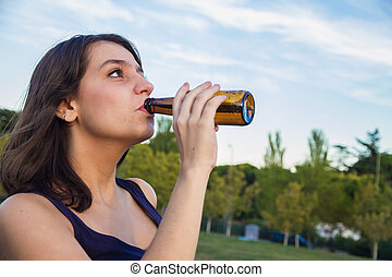 Pretty young brunette drinking from a bottle of beer in the park.