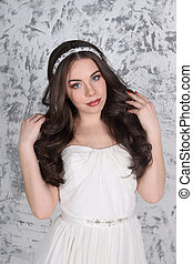 Pretty young brunette in diadem and with hairdo poses in white studio