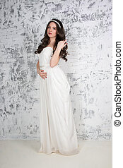 Pretty young brunette in long white dress poses near wall in white studio