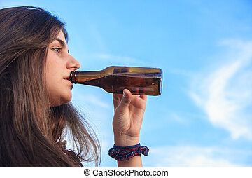 Pretty young brunette with blue eyes drinking from a bottle of beer in the park.