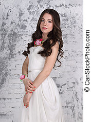 Pretty young brunette with bright jewerly and with hairdo poses in studio