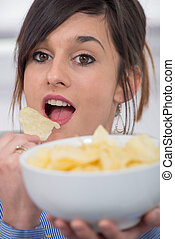 young brunette woman eating chips