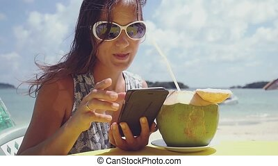 Pretty young brunette woman wearing sunglasses sends...