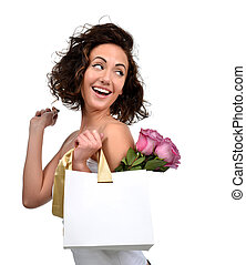 Pretty young brunette woman with shopping bag gold stripes and purple roses flowers